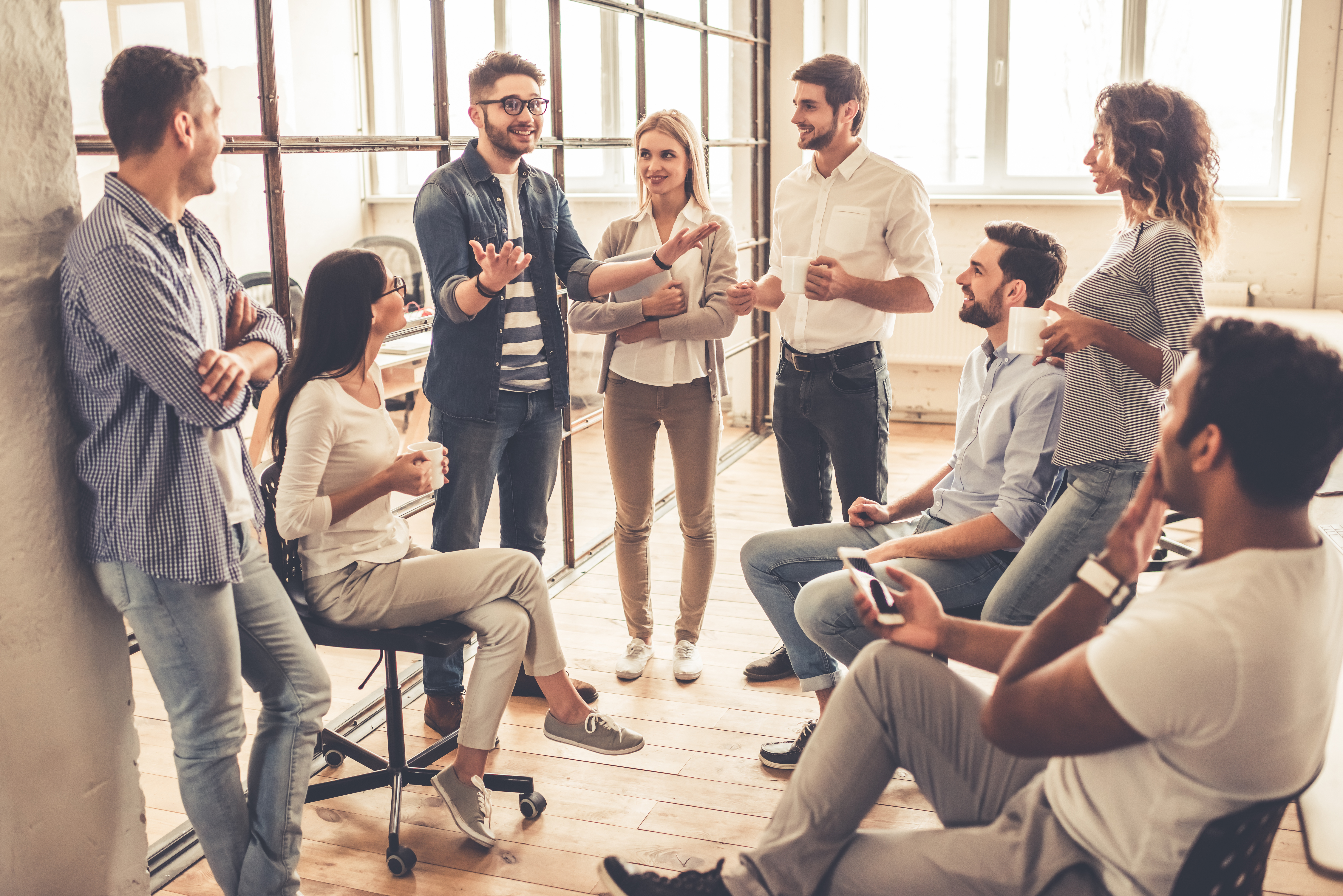 stock-photo-successful-young-business-people-are-talking-and-smiling-during-the-coffee-break-in-office-604204226